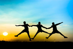 Silhouette of a children. Silhouette children jumping raised hands up on meadow background Royalty Free Stock Photo