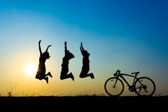 Silhouette children jumping. Silhouette of young woman jumping on sunset sky with bicycle on the prairie at yellow evening horizon sea yellow sunset heaven Stock Image
