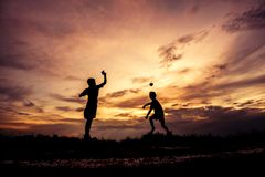 Silhouette of children playing paper airplane at sunset Royalty Free Stock Image