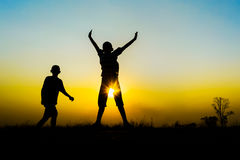 Silhouette of a children playing. Silhouette of children playing on sunset background Royalty Free Stock Image