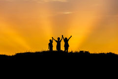 Silhouette children stand holding raised hands up on sunset. Stock Images