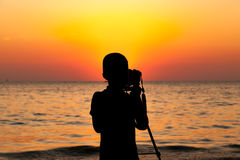 Silhouette of the children using dslr camera and tripod take photo of sunset on the beach., with beautiful light of sunset. Behind Stock Image