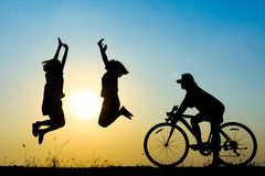 Silhouette children. Silhouette of young woman cyclist and jumping on sunset sky with stop on the prairie at yellow evening horizon sea yellow sunset heaven Stock Image
