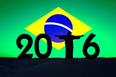 2016, silhouette of Christ the redeemer. In Rio de Janeiro, brazilian flag in the background Royalty Free Illustration