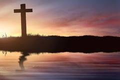 Silhouette of christian cross on the field with blur reflection. In lake water at sunset Royalty Free Stock Images