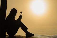 Silhouette of christian Man holding a cross cross in hands praying for blessing from god on sunlight background, hope concept stock photos