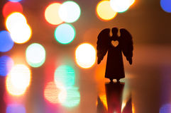 Silhouette of Christmas angel with hole in form of heart Stock Photos