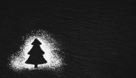 Silhouette of a Christmas tree drawn with white flour stock images