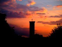 Silhouette of church in front of sunset and orange sky royalty free stock photo