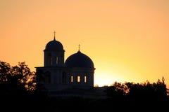 Silhouette of churches on a golden sky Stock Photos