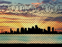 Silhouette of the city behind a fence Stock Images