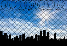 Silhouette of the city behind a fence topped Royalty Free Stock Image