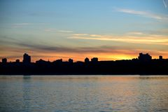 Silhouette of the city by the river at sunset. Royalty Free Stock Photo