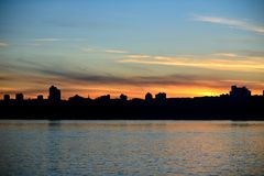 Silhouette of the city by the river at sunset. Stock Images