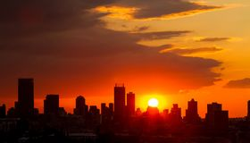 Silhouette City Sunset in Johannesburg South Africa. Dramatic cloudy sky at sunset in urban area. Silhouette buildings and lens flare from the sun stock image