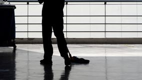 Silhouette of cleaning service people sweeping floor. Silhouette image of cleaning service people sweeping floor with mop and other equipment on trolley Stock Photos