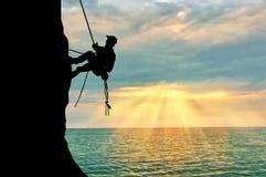 Silhouette climber climbing a mountain Royalty Free Stock Photography