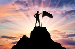 Silhouette of a climber with a flag on the top of the mountain which he subdued stock photos