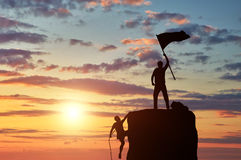 Silhouette climber leader with a flag on top of and rival Stock Photos