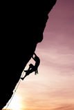 Silhouette of climber on rock face vertical image Royalty Free Stock Photos