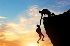 Silhouette of a climber saves another climber pulling him from the abyss royalty free stock images
