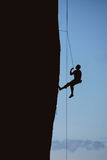 Silhouette of climber on sheer cliff Stock Images