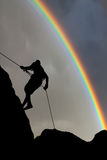 Silhouette of a climber on sunset sky with rainbow. Silhouette of a climber on sunset sky background with rainbow stock image