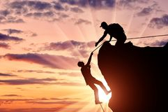 Silhouette of a climber who helps to climb the top of a man, throws him a rope and holds out his hand. royalty free stock photo
