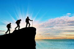 Silhouette climbers ascending to top of mountain Royalty Free Stock Images