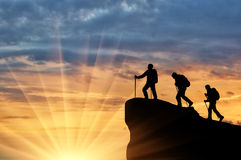Silhouette climbers ascending to top of mountain Stock Photography