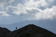 Silhouette of climbing young adult at the top of summit with aer Royalty Free Stock Image