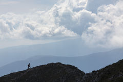 Silhouette of climbing young adult at the top of summit with aer Stock Photo