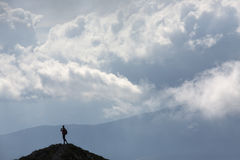 Silhouette of climbing young adult at the top of summit with aer Royalty Free Stock Images