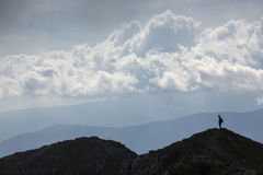 Silhouette of climbing young adult at the top of summit with aer Royalty Free Stock Photography