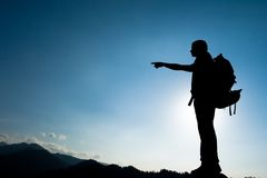 Silhouette of climbing young adult at the top of summit Stock Image
