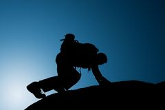 Silhouette of climbing young adult at the top of summit Royalty Free Stock Photo