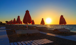 Silhouette closed umbrella with sunbeds at the beach and sunset Royalty Free Stock Photography