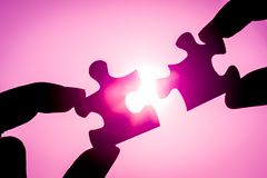 Symbol of association and connection concept. business strategy. Silhouette of closeup woman`s hand connecting a piece of jigsaw puzzle over sunlight effect Stock Photos