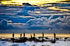 Silhouette and cloudy sky. Seven children in silhouette having fun while walking in the beach few minutes before sunset. in the background is stormy  cloud Royalty Free Stock Photography