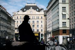 Silhouette of coachman with horse-drawn carriage in Vienna. Horse-drawn carriage fiaker with silhouette of coachman as tourist guide walking along the ancient Stock Image