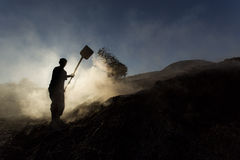 Silhouette of coal man working at sunset in smoke Stock Photos