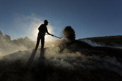 Silhouette of coal man working at sunset in smoke.  Stock Photo