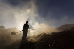 Silhouette of coal man working at sunset in smoke Stock Images