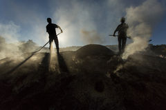 Silhouette of coal man working at sunset in smoke Stock Photo