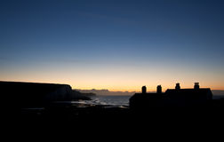 Silhouette of coastguard cottages at Seaford Head at sunrise Stock Photography