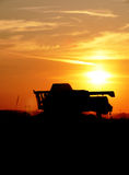 Silhouette - Combine Harvester. Combine harvester in evening action Stock Photos