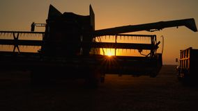 Silhouette of combine harvester pours out wheat into the truck at sunset. Harvesting grain field, crop season. stock footage