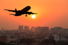 Silhouette commercial plane flying over city during sunset Stock Images