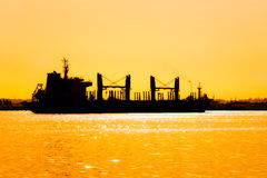Silhouette of a commercial ship at sunset Stock Images