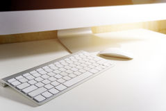 Silhouette of computer and keyboard with flare light in the offi Stock Images